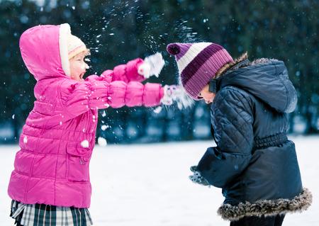 ni�as peque�as: Adorables ni�as que juegan en la nieve Juntos.