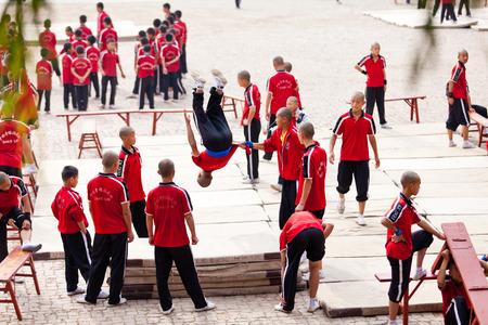 actividad fisica: Shaolin, China - 20 de octubre 2011: estudiantes de Shaolin estaban haciendo gimnasia en la calle. Los escolares vestidos con ropa deportiva tradicional escuela de Shaolin.
