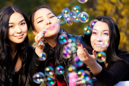 pakistani ethnicity: Young Asian Womens Blowing Bubbles in the park.