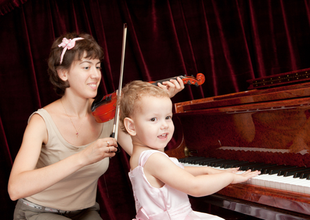 Mother and daughter playing piano and violin. photo