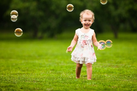 3 persons only: Blow bubbles. Cute girl with bubbles in the park