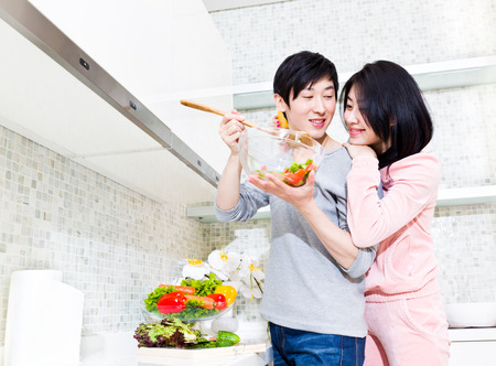 vegetables young couple: Husband and wife preparing food in the kitchen.