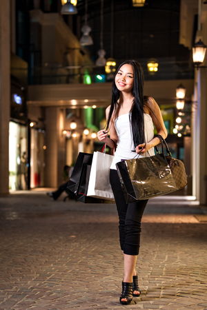 A happy asian woman shopping with shopping center background photo