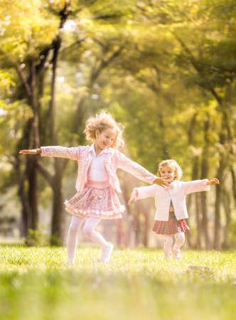ni�os sonriendo: Dos ni�as juegan en el parque. Foto de archivo