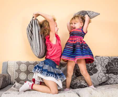 combate: Dos ni�os que se divierten en la lucha de almohadas con plumas en el aire saltando, riendo y riendo.