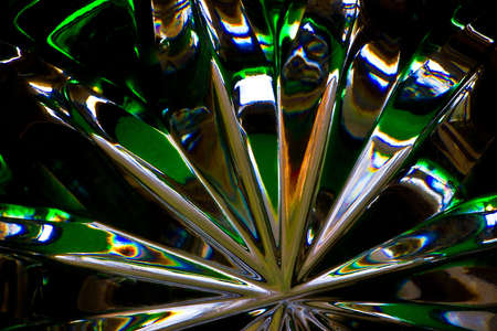 Abstract of the lines, reflections and colors of the bottom of a green crystal goblet. 写真素材