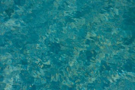 Mottled blues and aquas with yellow speckles from the sun reflecting on pool water