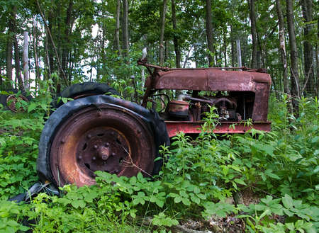 Rusting, broken, old tractor with flat tires sitting in a field, overgrown with green vegetation