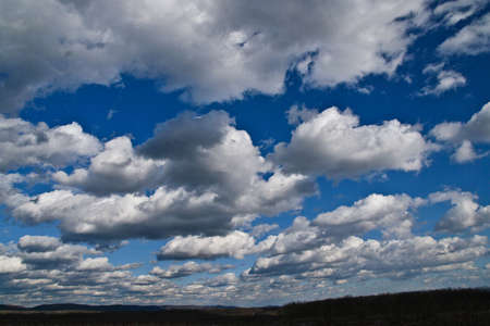 Background shot of the sky with interesting, light clouds drifting from the front of the frame to the horizon, over low, forest-covered mountains.