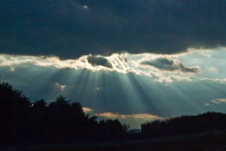 Crepuscular rays of the sun radiating from behind low blue clouds in late afternoon behind a silhouette of trees.
