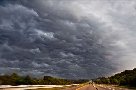 Photo of dark, scary, threatening storm clouds over highway, stretching into the horizon