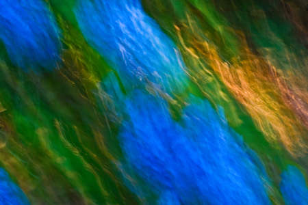 Abstract blur created by moving camera while shutter was open, creating graceful, diagonal lines of orange, yellow, blue and green