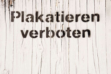 punishable: White wooden wall with text Plakatieren verboten