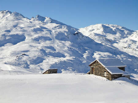Picturesque traditional cabin in the Alps in winter, snowy landscape