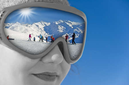 Close up of a girl with a ski mask reflection a snowy mountain landscape and the ski slope photo