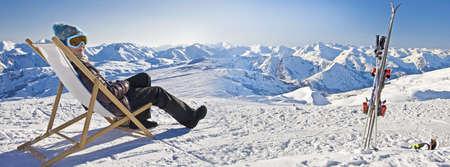 눈 덮인 스키 슬로프 근처 deckchair에서 일광욕 여자의 파노라마