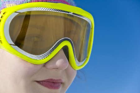 ski mask: Close up portrait of a smiling girl with ski mask, blue ski background