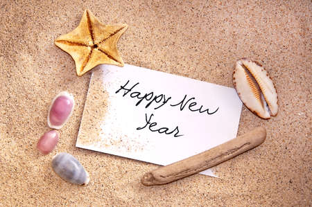 new message: Happy new year, written on a note in the sand with seashells