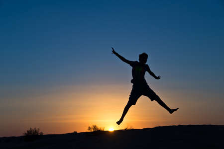 Silhouette of a boy jumping in the sun photo