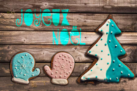joyeux: Gingerbread cookies on wooden background and text joyeux noel meaning  merry christmas in French