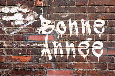 Bonne annee, meaning Happy new Year in French, on a brick wall, street-art style photo