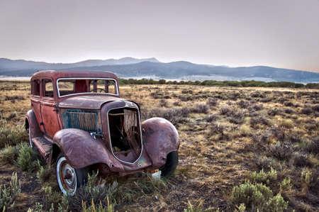 oxidado: Rusty coche destrozado, abandonado en la naturaleza