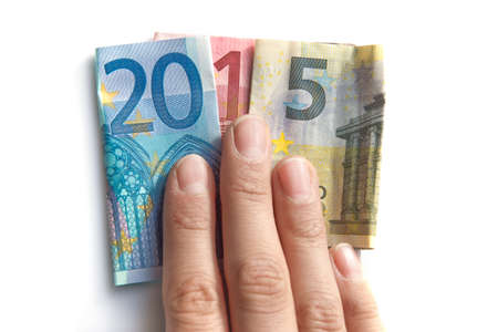 holiday budget: 2015 written with euros bank notes in a hand isolated on white background