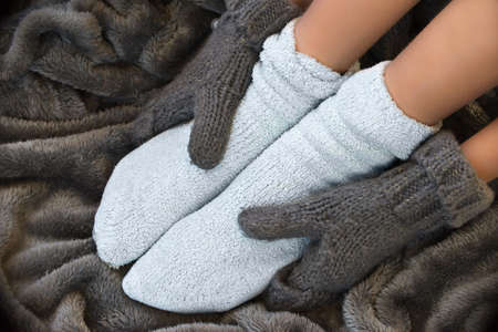 Feet in comfortable and warm woolen socks on a blanket