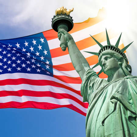 Statue of Liberty, zonnige hemel en de VS vlag achtergrond Stockfoto
