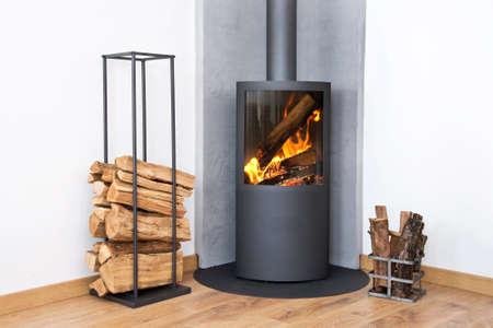 Modern burning stove next to a wood logs rack Archivio Fotografico