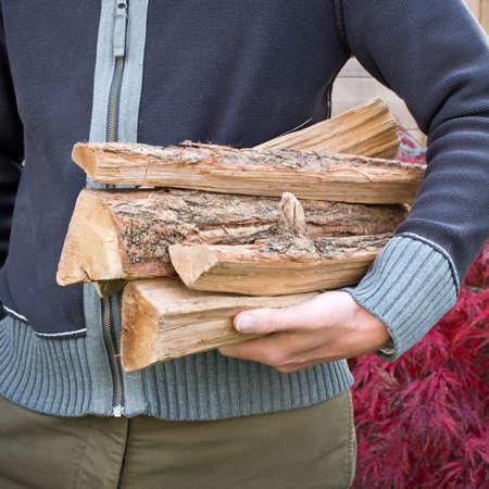 recoger: Hombre que lleva troncos de leña Foto de archivo