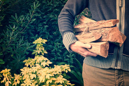 outdoor fireplace: Man carrying firewood logs, vintage process