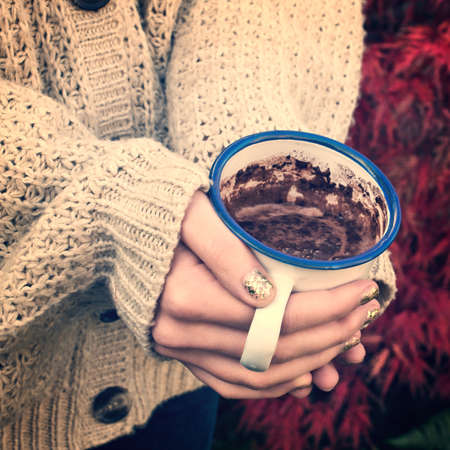 Close-up on girl hands with sweater holding a hot chocolate, vintage process photo