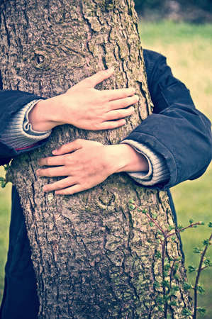Child embracing a tree trunk, vintage style photo