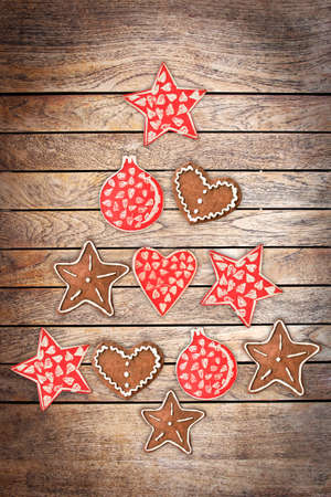 Collection of wooden rustic ornaments on wood planks background creating the shape of a Christmas tree photo