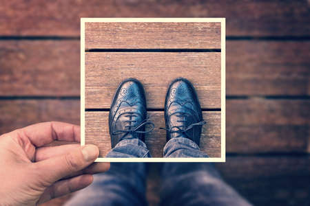 Selfie of foot and legs with black derby shoes seen from above with hand holding an instant photo frame, vintage process Stockfoto