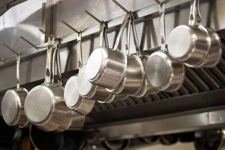the equipment: Muchos sartenes colgando en una cocina de un restaurante