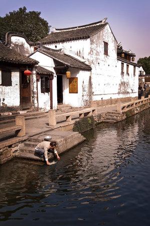 zhouzhuang: Zhouzhuang, China - A man washing dishes in the water of a canal.