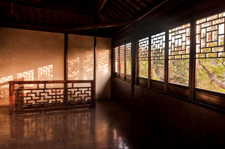 Wooden interior of a chinese house with sunlight and beautiful shadows