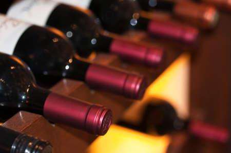Bottles of red wine on a wooden shelf