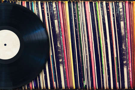 Vinyl record with copy space in front of a collection of albums (dummy titles), vintage process Banque d'images