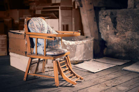 baby on chair: Old vintage baby chair in a dusty attic