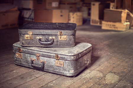 Old vintage suitcases in a dusty attic Фото со стока