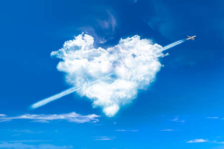 Heart shaped clouds in blue sky with plane photo