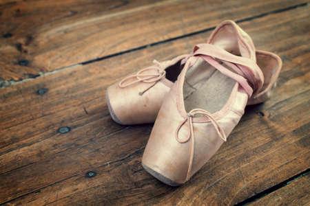 Zapatos de ballet rosados ??viejos en un piso de madera, proceso de vendimia Foto de archivo