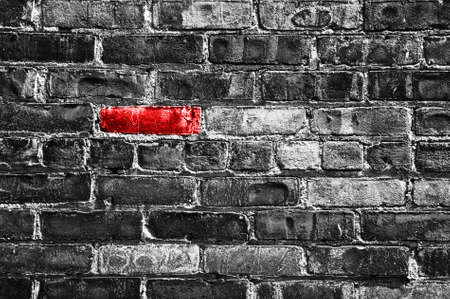 Red brick in a black and white wall Stock Photo