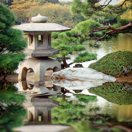 Stone lantern in a Japanese garden with water reflection Stock Photo