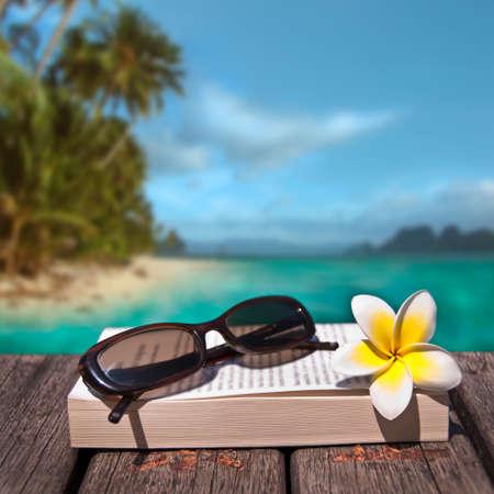Boek en zonnebril, tropisch strand achtergrond
