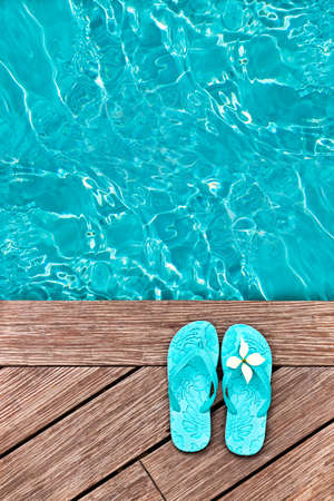 swimming shoes: Blue flip flops on a wooden deck
