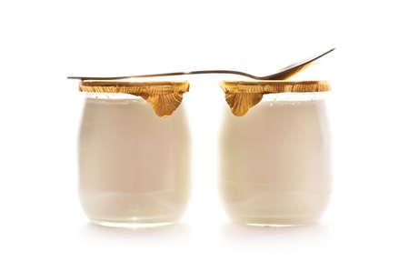 yogur: Dos yogures y una cuchara aislados sobre fondo blanco